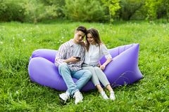 Young couple use phone sitting on inflatable sofa lamzac while resting on grass in park royalty free stock photo