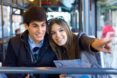 Young couple use their map and pointing where they want to go. Royalty Free Stock Image