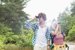 Young couple using binoculars while hiking in forest Stock Images