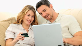 Young couple using a credit card on internet Royalty Free Stock Image