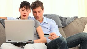 Young couple using a credit card on internet Royalty Free Stock Photography