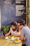 Young couple using digital tablet in cafeteria Royalty Free Stock Photography