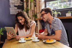 Young couple using digital tablet in cafeteria Stock Image