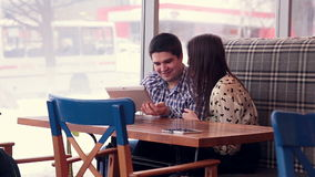 Young couple using digital tablet computer in cafe. Young couple using digital tablet computer in cafe - RED DRAGON stock footage