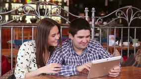 Young couple using digital tablet computer in cafe. Young couple using digital tablet computer in cafe - RED DRAGON stock video footage