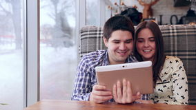 Young couple using digital tablet computer in cafe. stock video