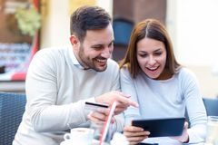 Young couple using a digital tablet and credit card for on line shopping. In outdoor cafe Stock Images