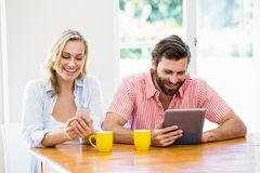 Young couple using digital tablet and mobile phone Stock Photography