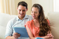 Young couple using digital tablet on sofa Stock Photography