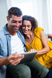 Young couple using a digital tablet on sofa Royalty Free Stock Image