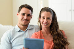 Young couple using digital tablet on sofa Royalty Free Stock Image
