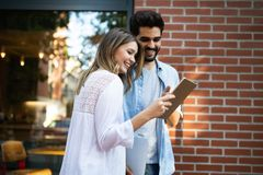 Young couple using a digital tablet together and smiling. Happy young couple using a digital tablet together and smiling stock image