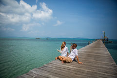 Young couple using digital tablet on wooden jetty Royalty Free Stock Images