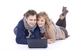 Young couple using a laptop. Young couple lying on the floor using a laptop Stock Photography