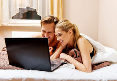 Young couple using laptop in bed Royalty Free Stock Image