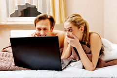 Young couple using laptop in bed Stock Photos