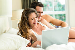 Young couple using laptop on bed Stock Photos
