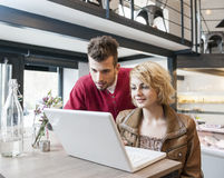 Young couple using laptop in cafe Stock Photo