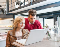 Young couple using laptop in cafe Stock Images