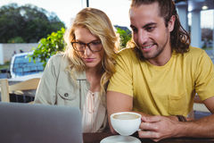 Young couple using laptop in cafeteria Royalty Free Stock Image