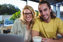 Young couple using laptop in cafeteria Royalty Free Stock Photo
