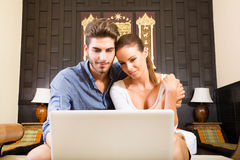 Young couple using a laptop computer in a asian hotel room Royalty Free Stock Photo