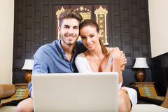 Young couple using a laptop computer in a asian hotel room Royalty Free Stock Image