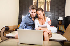 Young couple using a laptop computer in a asian hotel room Royalty Free Stock Images
