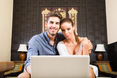 Young couple using a laptop computer in a asian hotel room Stock Photos