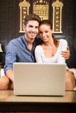 Young couple using a laptop computer in a asian hotel room Stock Images