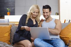 Young couple using laptop computer at home Stock Image