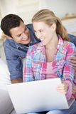 Young Couple Using Laptop Computer At Home Stock Images