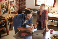 Young couple using laptop computer in kitchen, high angle Royalty Free Stock Photo