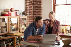 Young couple using laptop computer in kitchen, high angle Stock Photo