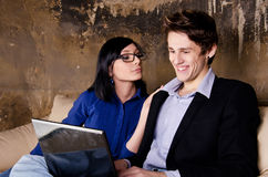 Young couple using laptop on couch Royalty Free Stock Images