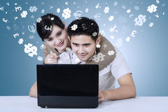 Young couple using laptop with currency symbols Stock Photos