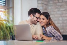 Young Couple Using Laptop. On Desk At Home Stock Image