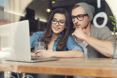 Young couple using laptop. Couple enjoying the wireless internet at cafe Royalty Free Stock Photo