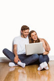 Young couple using laptop on floor Stock Photography