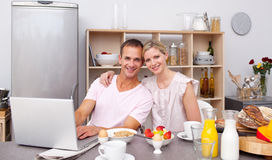 Young couple using a laptop while having breakfast Royalty Free Stock Photo