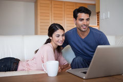 Young couple using a laptop while having a coffee Stock Photo