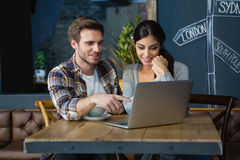 Young couple using laptop while having coffee Royalty Free Stock Images