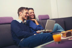 Young couple using a laptop at home and smiling Stock Image