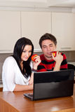 Young couple using laptop in kitchen Stock Images