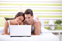 Young couple using laptop while lying on bed Stock Photography