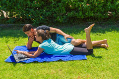 Young couple using a laptop lying on grass Royalty Free Stock Image