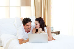 Young couple using a laptop lying on their bed Stock Photos