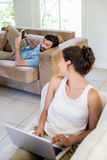 Young couple using laptop and mobile phone in living room Stock Photography