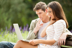 Young Couple Using Laptop At Park Stock Image