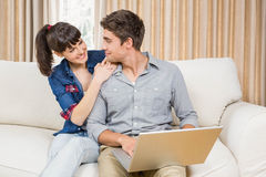 Young couple using a laptop. While sitting on a sofa in a living room Royalty Free Stock Photo